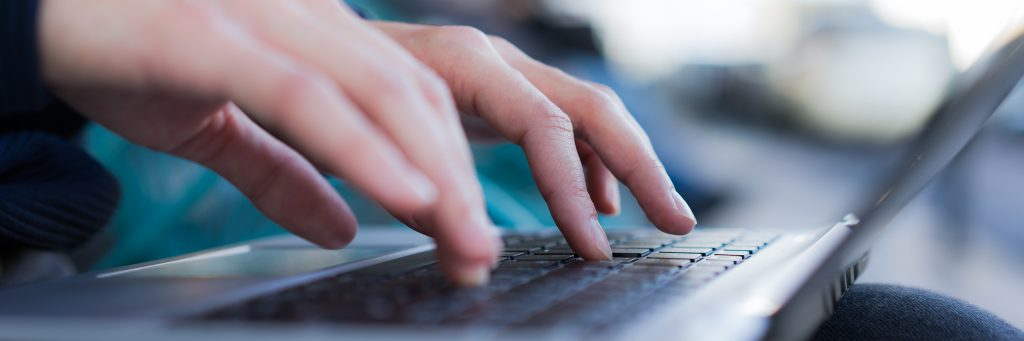 A picture of someone typing on his computer
